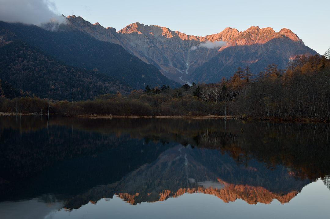 赤い穂高連峰が池に映り込む