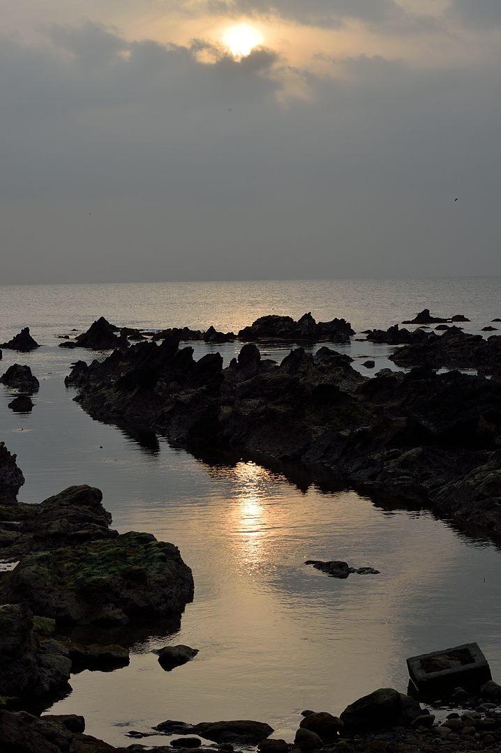 潮溜りに夕日が映り込む